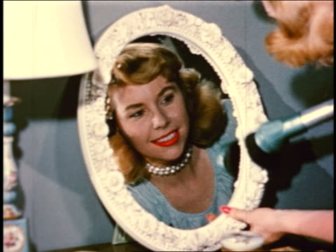 1950 close up hands of blonde woman with vacuum cleaner hose vacuuming small mirror frame on table