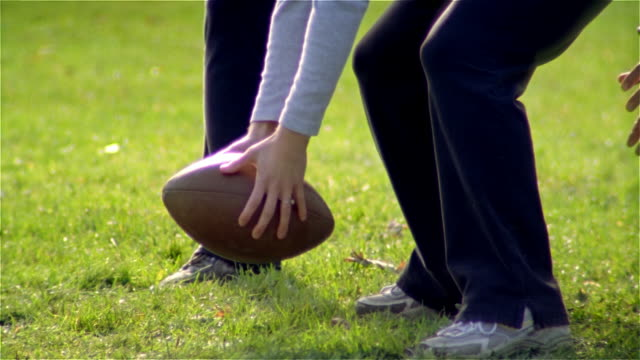 Close up hands of woman bent over, ready to snap ball in touch football game/ tilt up slow motion medium shot quarterback passing ball to woman who runs with it/ Maine