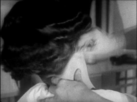 B/W 1926 close up hands of woman pulling hardened wax from nape of woman's neck  / newsreel