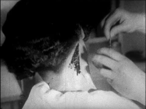 B/W 1926 close up hands of woman putting wax on nape of woman's neck  / newsreel
