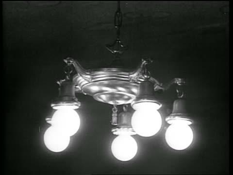 B/W 1928 close up hanging electric lamp becoming illuminated / Oklahoma / newsreel