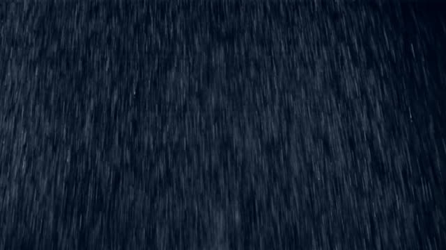 Close up heavy rain falling against a black background