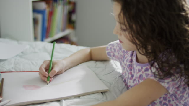 Close up high angle panning shot of girl drawing on sketchpad / Provo, Utah, United States