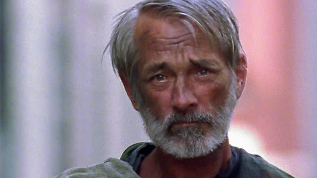 Close up homeless man with beard posing