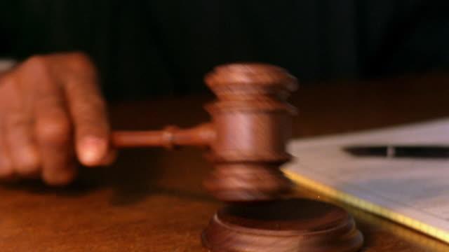 Close up judge's hand pounding gavel / tilt up Black senior judge posing