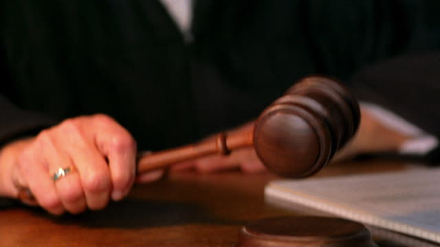 Close up judge's hand pounding gavel / tilt up female senior judge posing
