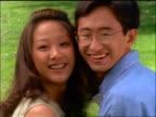 close up Korean teenage girl + boy turning to look at camera + smiling outdoors