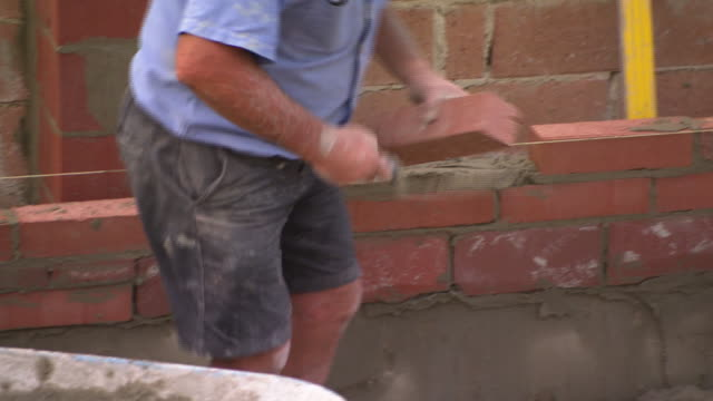 close up labourer clearing sand from laid drainage box at end of concrete slab / close up anon bricklayer laying mud on row of bricks lays and taps...