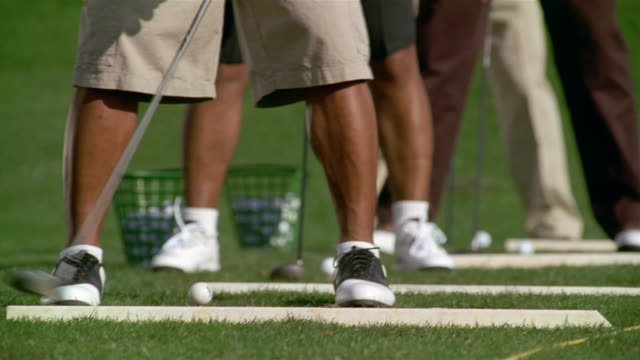 Close up legs and feet of four men standing in a row hitting golf balls on driving range
