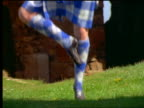 close up legs dancing / zoom out woman Highland dancing + man playing bagpipes near castle ruins / Scotland