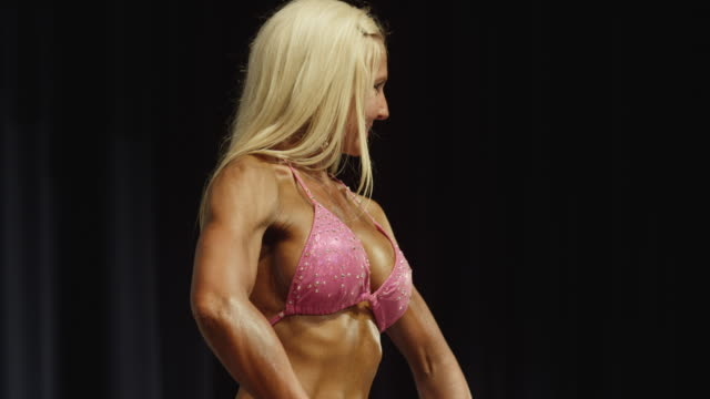 Close up low angle panning shot of bodybuilder posing on stage at competition / Draper, Utah, United States