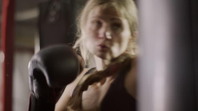 Close up low angle panning shot of female boxer hitting heavy bag / Lehi, Utah, United States