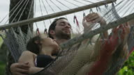 Close up low angle shot of couple relaxing in hammock / Esterillos, Puntarenas, Costa Rica