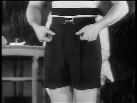B/W 1937 close up male model moving fingers down pleats of bathing suit