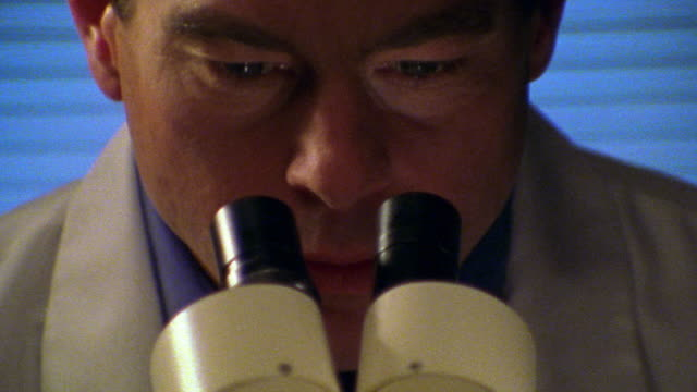 close up male scientist bending down + looking through microscope