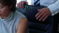close up man coming up behind upset businesswoman at desk + rubbing her arm (sexual harassment)