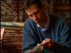 close up man examining Oriental rug in store / Istanbul, Turkey