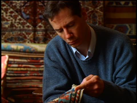 close up man examining Oriental rug in store / Istanbul, Turkey