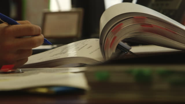 Close up, man flips pages of book