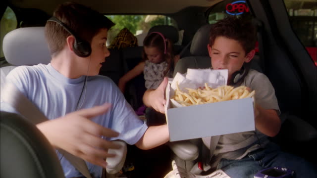 Close up man handing tray of fast food to children in car / boys handing out food