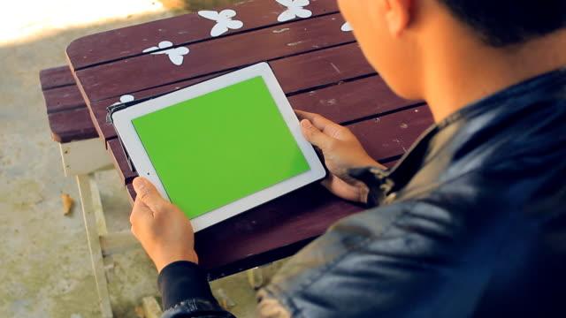 Primo piano di uomo tenendo vuota Tablet PC con schermo verde