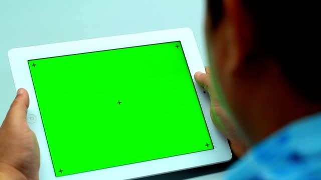 Primo piano di uomo tenendo vuota Tablet PC con zona verde