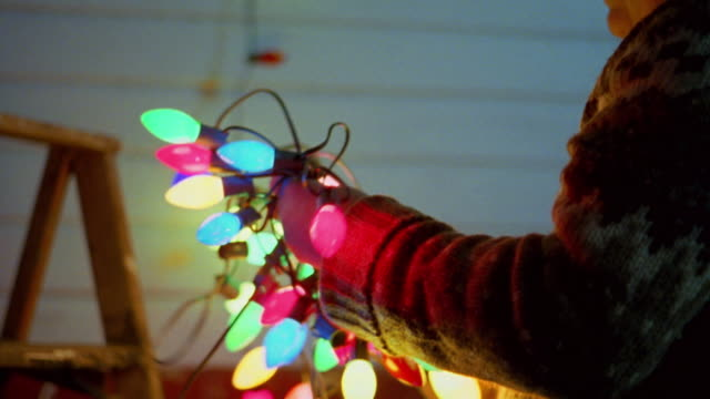 Close up man holding string of Christmas lights w/ladder in background against wall