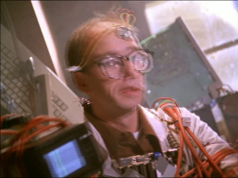CANTED close up man in glasses strapped to computers crossing fingers / lights flicker + man shakes