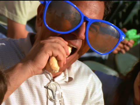 CANTED close up man in large sunglasses eating hot dog in stadium