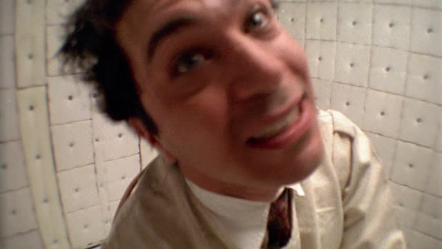 FAST MOTION close up man in straitjacket making faces at camera in padded room