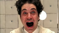 Close up man in straitjacket with wild hair making faces to camera in padded room