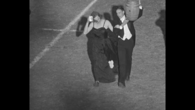 Close up man in tuxedo dances with woman in evening gown on football field as band plays / tuxedo man carries beer keg on shoulder woman on his arm...