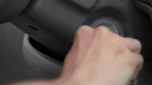 Close up man inserting key into car's ignition and turning it