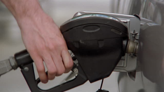 Close up man inserting nozzle of gas pump into gas tank / squeezing trigger