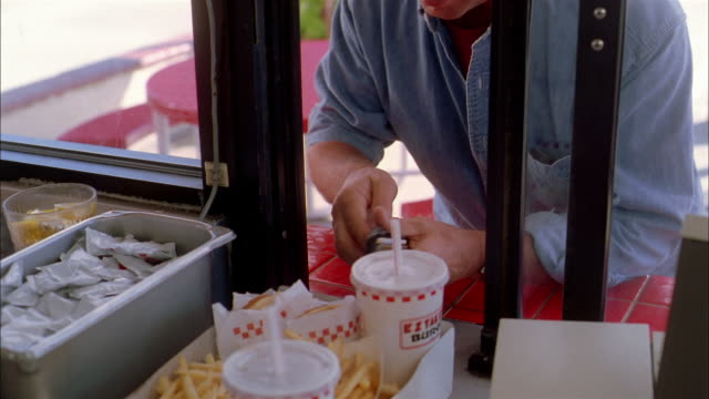 Close up man paying for food at window of fast food restaurant