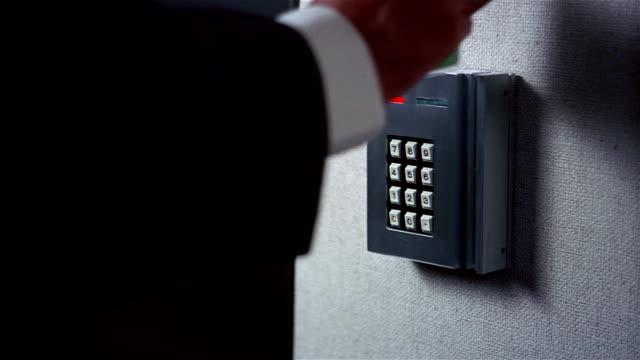 Close up man swiping card through security pad / green light turning on / sliding door opening