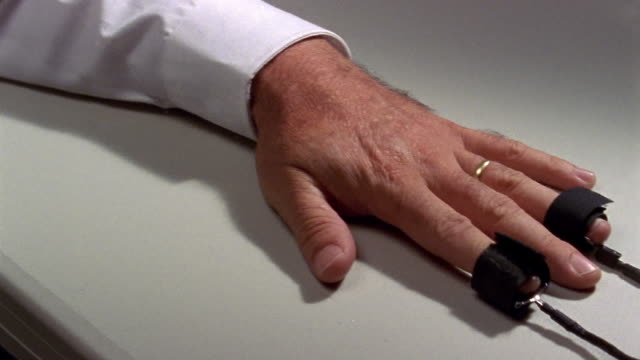 Close up man's hand connected to lie detector