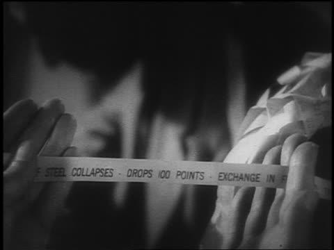 B/W 1929 REENACTMENT close up man's hand holding ticker tape showing stock market crash