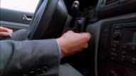 Close up man's hand inserting key into ignition / turning key