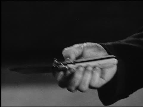 B/W close up man's hand opening switchblade