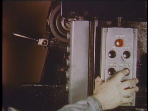 1950 close up man's hand pushes reset button on newspaper printing press