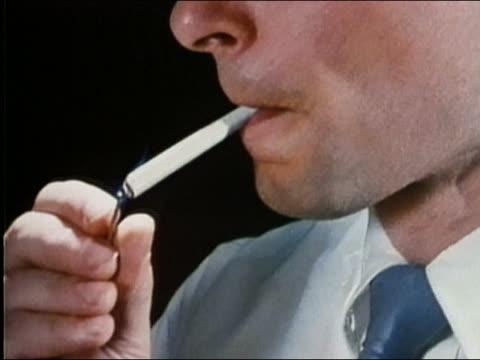 1987 close up man's hand striking match / pan lighting cigarette, taking drag and exhaling