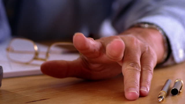 close up man's hand tapping fingers on table / paper + eyeglasses in background