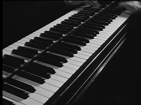 B/W close up man's hands playing piano quickly up + down keyboard / reflected in piano surface