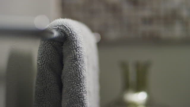 Close up man's hands take small towel from a rack at the bathroom sink.