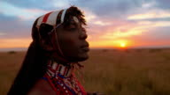 close up Masai tribesman looking around + then at camera with sunset in background / Kenya