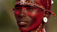 close up Masai tribesman turning + looking at camera while smiling with face paint / Kenya