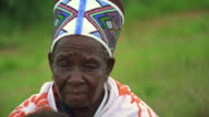 Close up mature Black Zulu woman in colorful hat outdoors / Durban, KwaZulu-Natal, South Africa