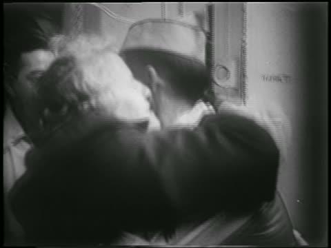 B/W 1953 close up PAN middle aged woman hugging kissing returning soldier / Korean War homecoming