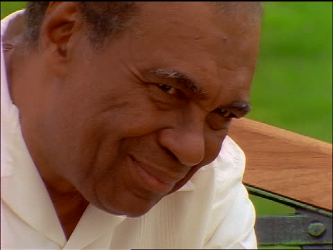 close up middle-aged black man looking at camera + smiling outdoors